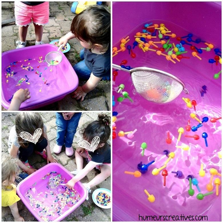 Les enfants attrapent les pions dans l'eau avec une passoire (transvasement)