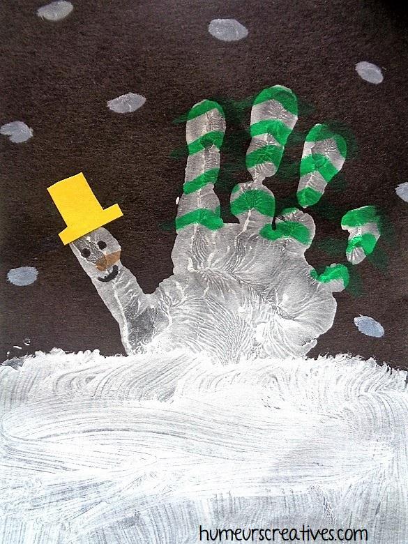Une montagne d'hiver en empreinte de main avec bonhomme de neige et sapins