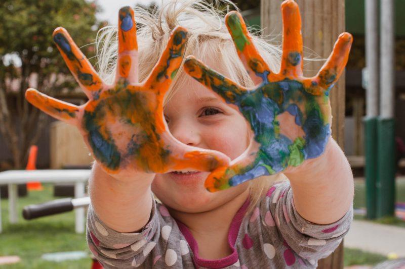petite fille avec les mains pleines de peinture