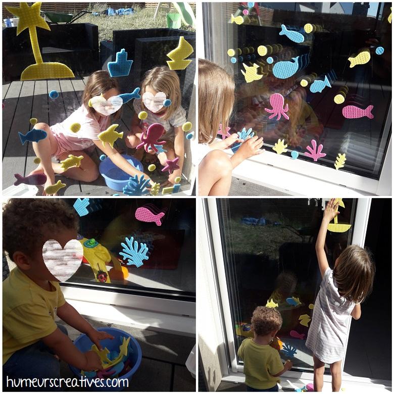 les enfants créent des dessins sur les fenêtres avec les éponges