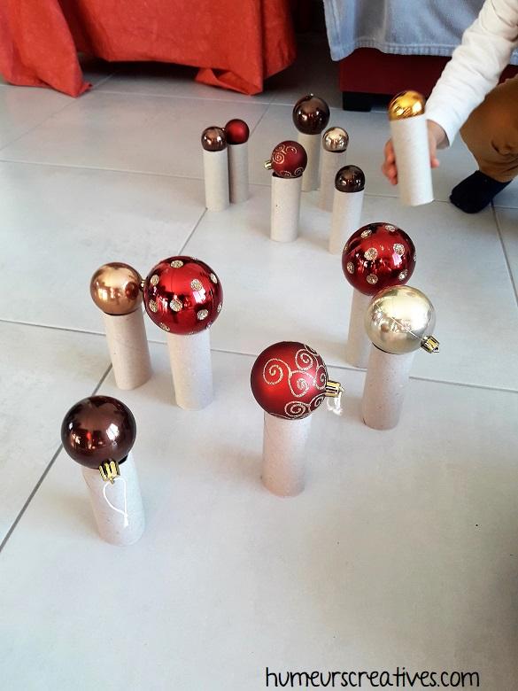 jeu de noel pour enfants : positionner les boules sur les rouleaux de papier toilette